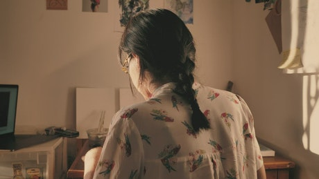 Artist seen from behind painting in her studio