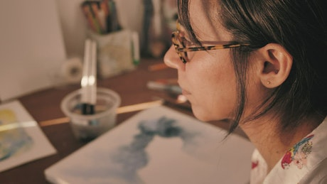 Artist soaking her paintbrush to paint with watercolors