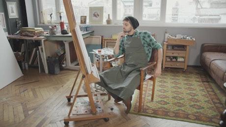 Artist stares at canvas sitting in art studio