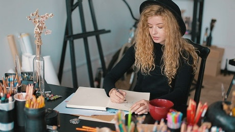 Artist thinking and sketching sips cup of tea
