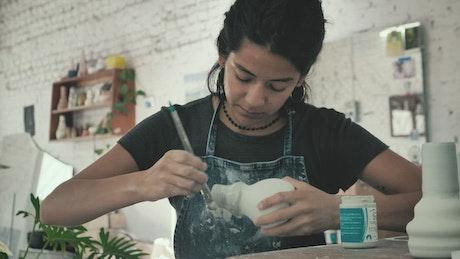 Artist varnishing a vase