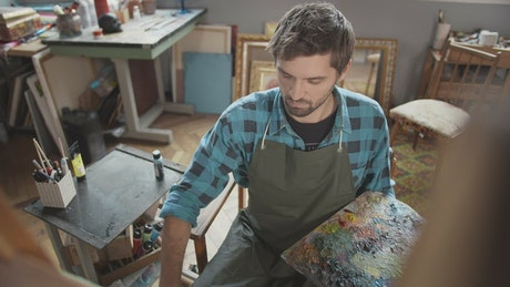 Artist with palette thinks about ideas while looking at canvas