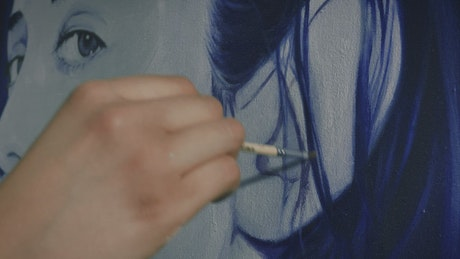 Artist's hand painting the hair of a portrait
