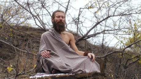 Ascetic Yogi sitting in nature meditating