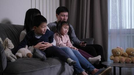 Asian family enjoying a TV show