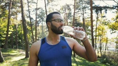 Athlete man drinking water during his training