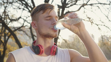 Athlete man drinking water in his training