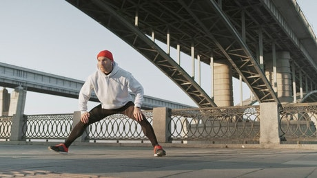 Athlete stretching his legs in the street