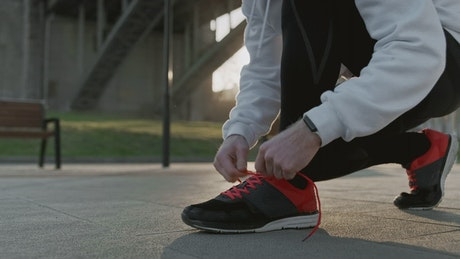 Athlete tying shoelaces before training