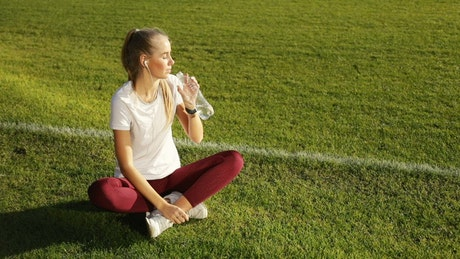 Athlete woman drinking water and resting