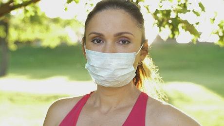 Athlete woman wearing mask in park, portrait