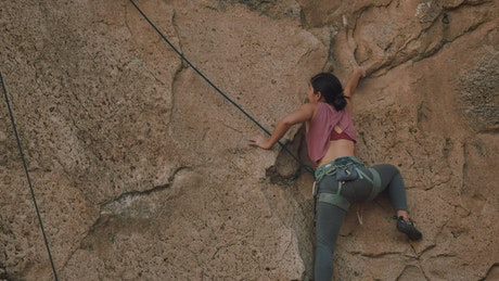 Athletic female mountaineer climbing a rocky mountain