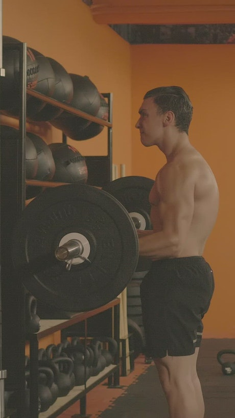 Athletic man doing reps with a large dumbbell