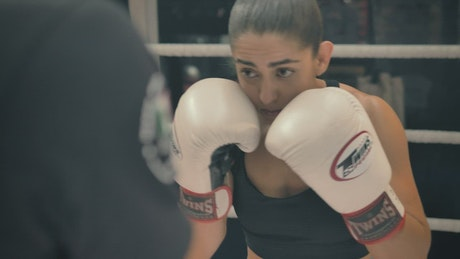 Athletic woman punching boxing pads