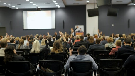 Audience raise hands at business conference