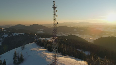 Aurora covering a forest with a communication tower