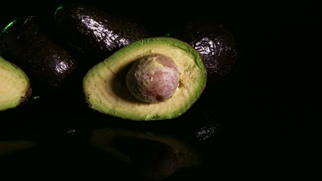 Avocado sliced in half on a dark background