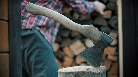 Ax stuck in a log while a lumberjack works