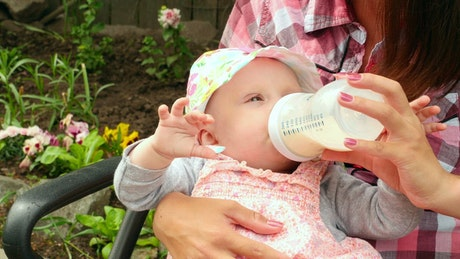 Baby girl drinking milk from a baby bottle