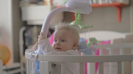 Baby girl holding onto her crib