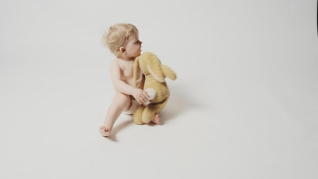 Baby girl with plushie sitting on a white background