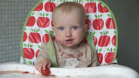 Baby having a meal and making a mess