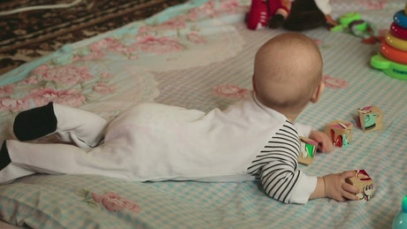 Baby playing with cubes over a blanket