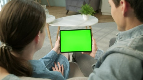 Back view of couple holding green screen tablet