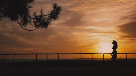 Backlit woman walking at sunset