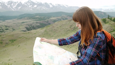 Backpacker checks her map from viewpoint