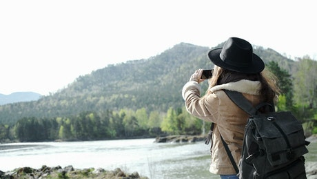 Backpacker takes panoramic photo of river and mountains