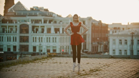 Ballerina in a red dress on a rooftop
