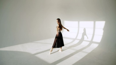 Ballerina spins in black tutu in sunlit white room
