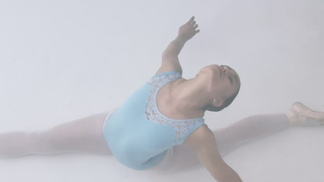 Ballerina while stretching on the floor