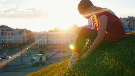 Ballet dancer adjusting her slippers on the grass