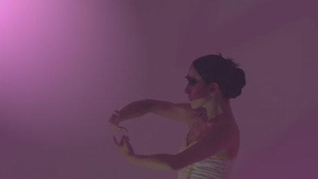 Ballet dancer moving her hands under a dim pink light