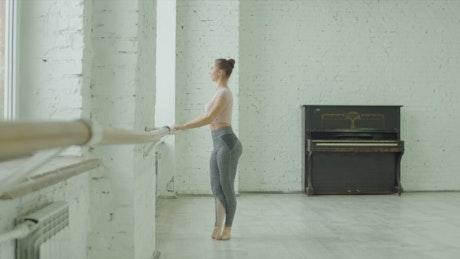 Ballet dancer stretching on a barre