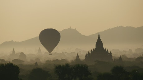 Balloon flying during sunrise over ancient temples