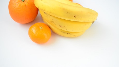 Bananas and oranges on white surface