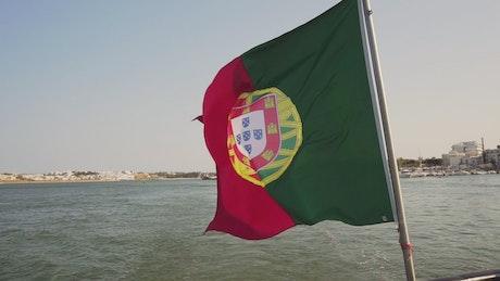 Bandera de portugal ondeando en el mar con la costa en el fondo