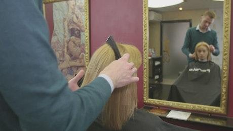 Barber combing blonde hair
