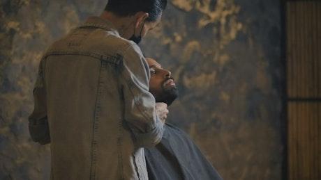 Barber grooming a man's beard