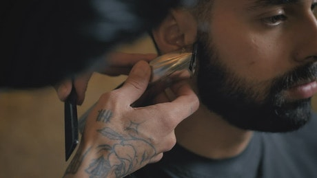 Barber outlining a client's beard