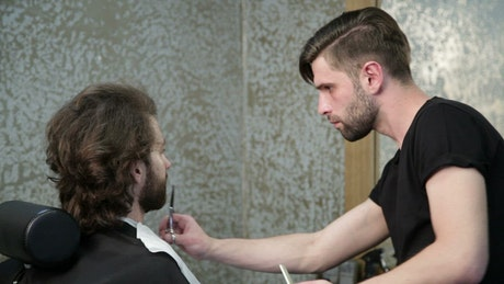 Barber trimming a beard