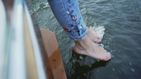 Barefoot woman touching the surface water