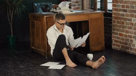 Barefoot writer sits on floor reading manuscript