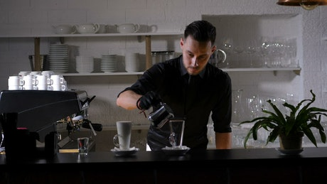 Barista filling a pitcher with milk