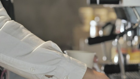Barista putting the lid on an espresso
