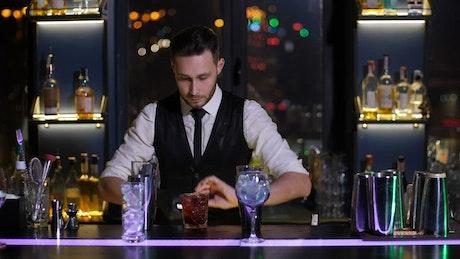 Bartender decorating drink glasses