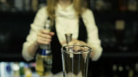 Bartender pouring shots into a mixer